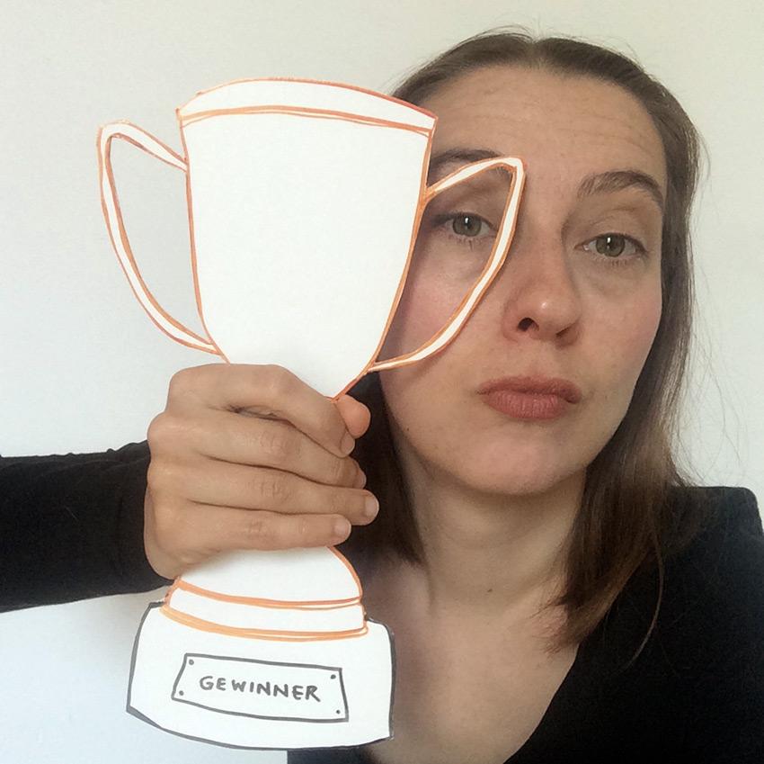 """Visualisierung von """"Gewinner sein"""", Roberta Bergmann hält einen Papp-Award in die Luft."""